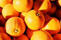 Oranges. Beautiful oranges for sale, showing off the contrast between light and shadow. Close-up stock photos