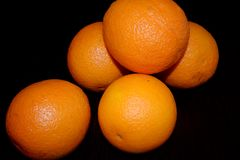 Oranges on a black background. Ripe oranges on a black background Stock Photo