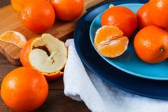 Oranges on the blue plate on dark wooden table. Oranges on the blue plate on dark wooden table Stock Photo