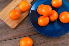 Oranges on the blue plate on dark wooden table. Oranges on the blue plate on dark wooden table Stock Photography