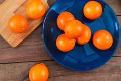 Oranges on the blue plate on dark wooden table. Oranges on the blue plate on dark wooden table Royalty Free Stock Photos