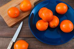 Oranges on the blue plate on dark wooden table. Oranges on the blue plate on dark wooden table Stock Images