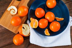 Oranges on the blue plate on dark wooden table. Oranges on the blue plate on dark wooden table Stock Image