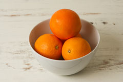 Oranges in a bowl. Four fresh juicy oranges inside a white coloured bowl that is placed on a rustic white coloured kitchen table royalty free stock photography