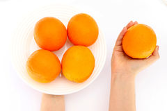 Oranges in a bowl in hand Stock Photo
