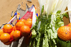 Oranges and celery. Fruit and vegetables hanging outside on a shop wall Stock Images