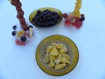 Oranges, cerises et tensions de fruit placées sur la neige Photographie stock libre de droits