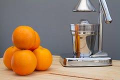 Oranges and chrome citrus juicer Royalty Free Stock Photo