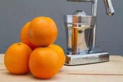 Oranges and chrome citrus juicer Stock Photos