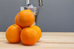 Oranges and chrome citrus juicer Royalty Free Stock Images