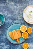 Assorted homemade ice cream with fresh fruits. Oranges and citrus popsicle ice pop and coconut sorbet in bowl. Top view, blank space Stock Photography