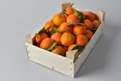 Oranges crate. Fresh and ripe orange fruits with leaves in a wooden crate  on white background. (landscape oriented Stock Image