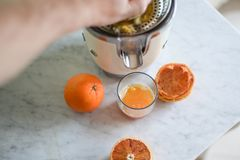 Male hand Squeezing oranges for a glass of fresh healty juice stock photo