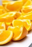 Oranges cut in quarters. Orange cut in quarters on a white plate Stock Image