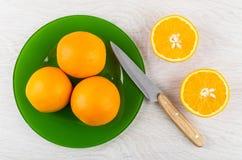 Oranges dans le plat, le couteau et les moitiés de l'orange sur la table Photos stock