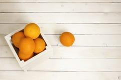 Oranges dans un boîtier blanc sur le fond en bois Image libre de droits