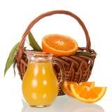 Oranges dans un panier, cruche avec du jus sur le blanc Image stock