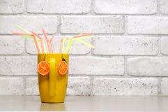 Oranges de boucles d'oreille sur la tasse avec des pailles de cocktail Images stock