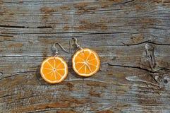 Oranges de boucles d'oreille sur le fond en bois Photos libres de droits