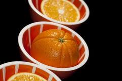 Oranges de totalité et de moitiés dans des cuvettes oranges sur le noir Image stock