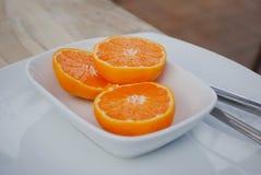 Oranges divisées en deux dans la cuvette blanche Image stock
