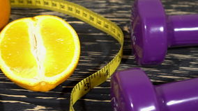 Oranges, dumbbells and measuring tape on wooden background. stock footage