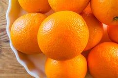 Oranges empilées sur le plateau de porcelaine sur le dessus de table en bois, vue supérieure Images stock