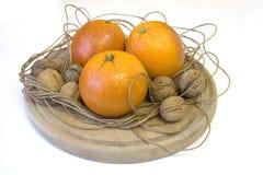 Oranges et noix sur un hachoir Image libre de droits