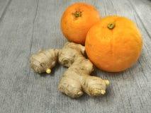 Oranges et racine de gingembre sur le bois Image stock