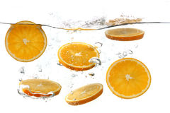 Oranges Falling Into Splashing Clear Water Stock Image