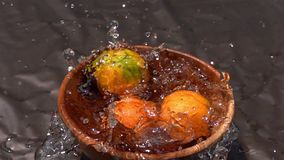 Oranges falling into the water in wooden bowl on dark background