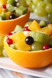 Oranges filled with green grapes, berries, kiwi and pears Stock Photo