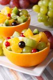 Oranges filled with green and red grapes, berries, kiwi Royalty Free Stock Photo