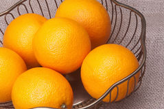 Oranges. Fresh oranges in an old metal bowl with a burlap background Stock Photos