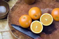 Oranges, fruit knife, cutting board Royalty Free Stock Image