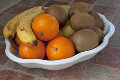 Oranges and fruits. Oranges, bananas, apples and kiwis in a tray Royalty Free Stock Photos