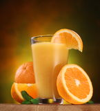 Oranges and glass of juice. Stock Photos