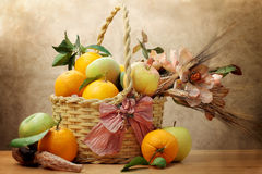 Oranges and green apple inside wicker basket Royalty Free Stock Photos