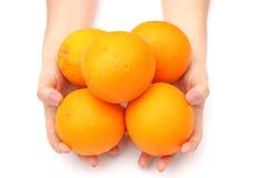 Oranges in hand Stock Photos