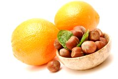 Oranges and hazelnuts in a marble bowl. Oranges and hazelnuts with mint leaves in a round marble bowl, everything isolated on a white background royalty free stock image