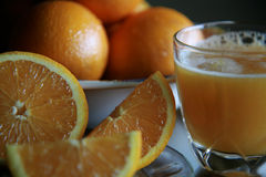 Oranges and juice. Fresh orange juice, sliced oranges and bowl of oranges in background Royalty Free Stock Images