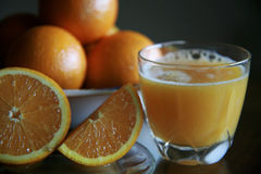 Oranges and juice. Glass of orange juice with sliced oranges and bowl of oranges in background Royalty Free Stock Image