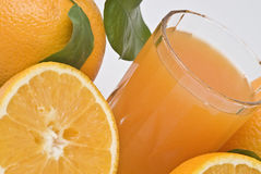 Oranges and juice in the foreground. Royalty Free Stock Photos