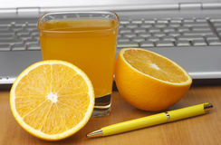 Oranges, juice and laptop Royalty Free Stock Photography