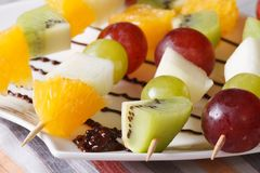 Oranges, kiwi, grapes and pears on skewers macro horizontal Royalty Free Stock Images