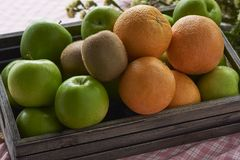 Oranges,kiwis and apples in a wooden crate. A wooden crate containing oranges, kiwi and apples royalty free stock photography