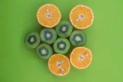 Oranges and kiwis cutted on half on green surface. Up view of oranges and kiwis cutted on half on green surface stock images