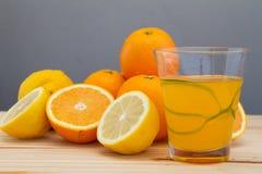 Oranges and lemon with slices and glass of fresh orange juice Stock Photo