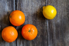 Oranges and lemon. On textured weathered wooden table - top view stock photos