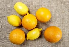 Oranges and lemons on jute background Stock Photos